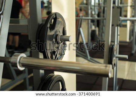 Training apparatus in gym hall. Weight plates hanging on metal rack in gym. Training apparatus on background.