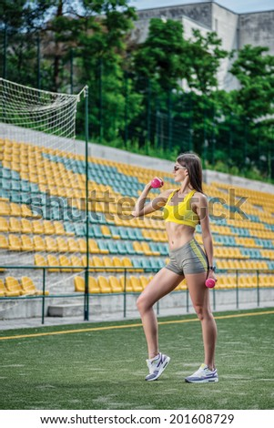 Training biceps and strength training on women's hands. Fitness woman in tracksuit and dumbbell training on the football field on a hot sunny day. - stock photo