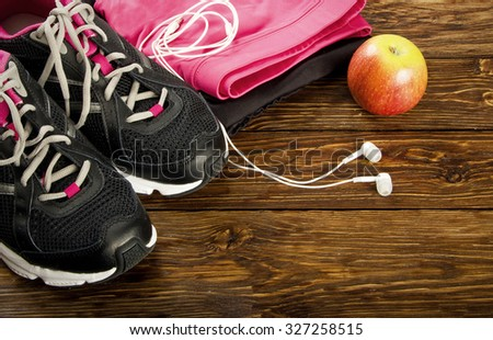 Training clothes and shoes on a wooden background - stock photo