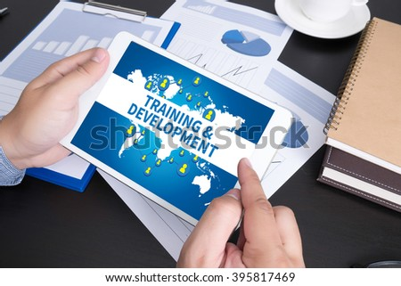 TRAINING & DEVELOPMENT CONCEPT, Modern people doing business, graphs and charts being demonstrated on the screen of a touch-pad, - stock photo