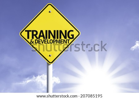 Training & Development road sign with sun background  - stock photo