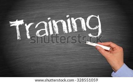 Training - female hand writing text on chalkboard - stock photo