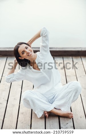 Training her body and soul. Beautiful young smiling woman in white clothing performing yoga outdoors - stock photo