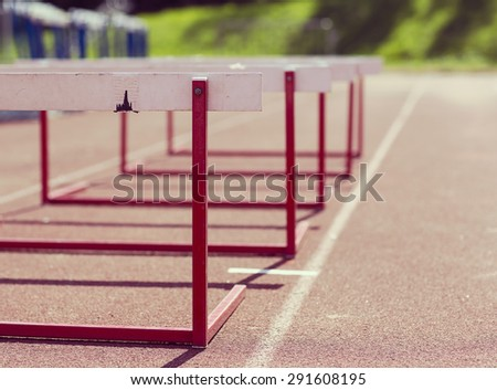 Training hurdles in the track. Image taken in the summer time and image has a vintage effect. - stock photo