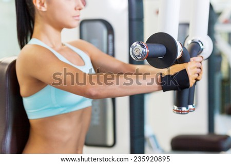 Training in gym. Cropped image of attractive young woman working out in gym - stock photo