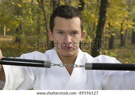 Training Nunchaku in nature, and the autumn woods - stock photo