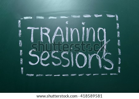 Training sessions inscription written with white chalk on blackboard - stock photo