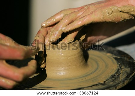 Training to potter's skill on a potter's wheel with damp clay. Close up.