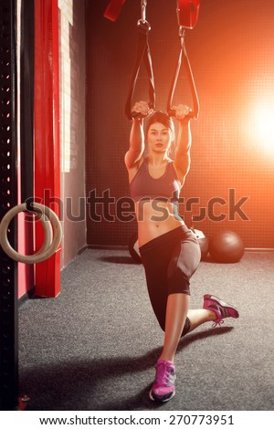 Training TRX straps. Attractive muscular brunette woman in gray clothes, doing fitness on the red belts TRX in the gym - stock photo