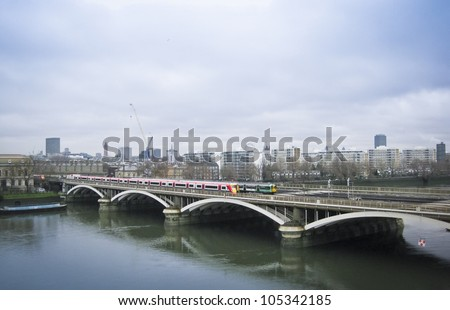 trains from victoria station crossing battersea bridge across the river thames in london england on an overcast morning - stock photo
