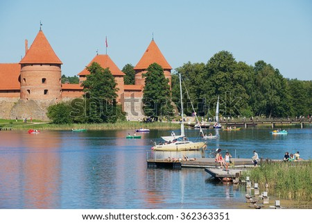 TRAKAI, LITHUANIA - AUGUST 02, 2015: Unidentified people sunbathe at Galve lake with the Trakai castle at the background on a hot summer day in Trakai, Lithuania.