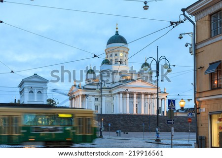 Tram passing by Helsinki Senate Square with Helsinki Cathedral in the background - stock photo