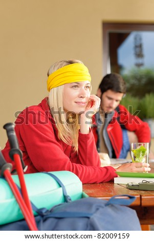 Tramping young couple backpack relax sitting by wooden table cottage