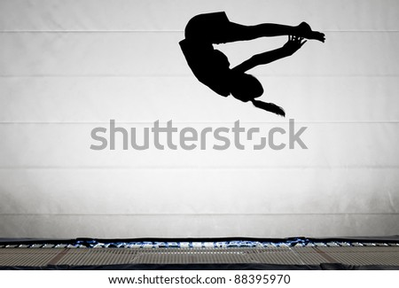 trampoline girl with pike somersault - stock photo