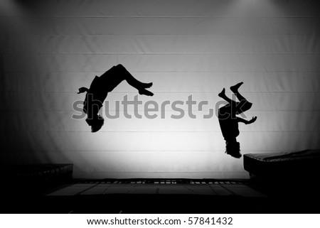 trampoline silhouette friends somersault - stock photo