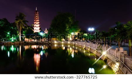 Tran Quoc pagoda at night view in Hanoi. This pagoda is located on a small island near the southeastern shore of West Lake. This is the oldest Buddhist temple in Hanoi, Vietnam. Panoramic style - stock photo