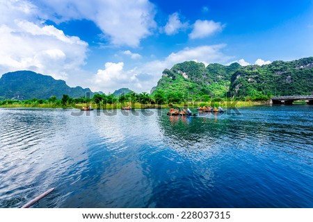 TRANG AN ECO-TOURISM SITE, NINHBINH, VIETNAM - NOVEMBER 2, 2014 - Visitors voyaging along a waterway, sightseeing. This location is very famous for beautiful landscape. It's a UNESCO heritage site. - stock photo