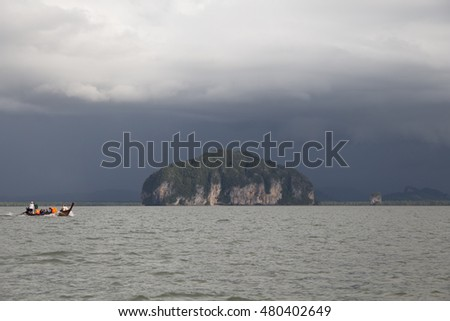 Trang, Thailand - December 10, 2015: Tourists in long tail boat come to visit Golden Scale Dragon Spine Beach in Palian of Trang - can see when low tide of sea leve made by nature with a lot of shell.