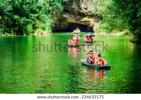 TRANGAN ECO-TOURIST COMPLEX, VIETNAM - NOVEMBER 27, 2014 - Tourists travelling by boat in front of a cave. This is a UNESCO site and very famous for its beauty of caves, temples & natural beauty. - stock photo