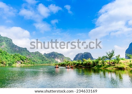 TRANGAN ECO-TOURIST COMPLEX, VIETNAM - NOVEMBER 27, 2014 - Tourists travelling by boat on the lagoons inside. This is a UNESCO site and very famous for its beauty of caves, temples & natural beauty. - stock photo