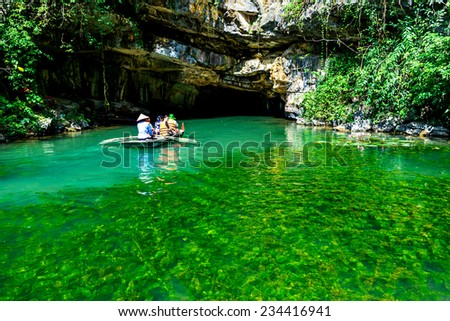 TRANGAN ECO-TOURIST COMPLEX, VIETNAM - NOVEMBER 27, 2014 - Visitors travelling by boat in a stream full of seaweed alga. This location is very famous for beauty of caves, temples & natural beauty. - stock photo
