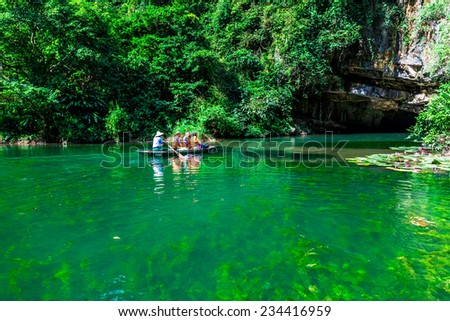 TRANGAN ECO-TOURIST COMPLEX, VIETNAM - NOVEMBER 27, 2014 - Visitors travelling on boats. This location is very famous for beauty of caves, temples & natural beauty, it's been approved a UNESCO site. - stock photo