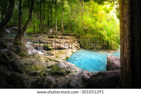 Tranquil and peaceful nature background of beautiful river stream flowing through natural cascades and wet stones with sunlight shining gently  - stock photo
