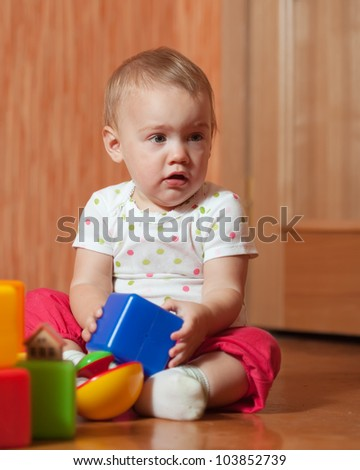 tranquil baby girl plays with toy blocks in home