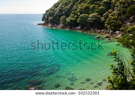 Tranquil bay framed by lush subtropical forest of Abel Tasman National Park, South Island, New Zealand - stock photo