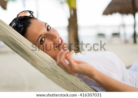 Tranquil beautiful woman relaxing lying on a hammock at tropical beach. Summer vacation relax and tranquility concept. Relaxed female resting outdoor. - stock photo