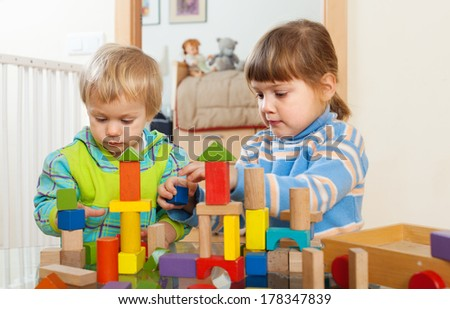 tranquil children playing with wooden toys in home interior - stock photo