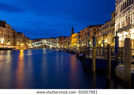 Tranquil, evening scene in the Rialto district in Venice. View of the famous Rialto bridge spanning the Grande Canal, with lights along the canal's walkways lighting up the historic buildings.