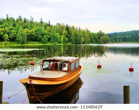 Tranquil Finnish landscape: single boat in a calm lake - stock photo