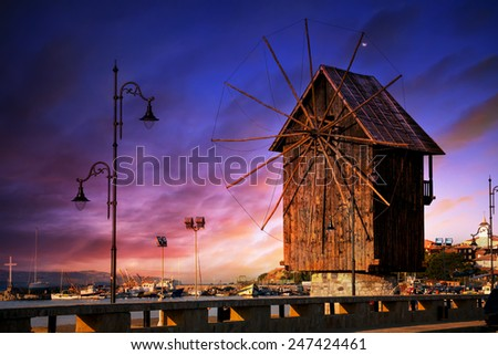Tranquil HDR sunset scene in a peaceful evening with fishing boats docked in the harbor on Nesebar, Bulgarian famous sea resort  - stock photo