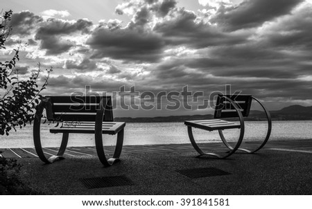 Tranquil Idyllic Scene on the Lake Garda Waterfront. Idyllic scene and dramatic sky in black and white. - stock photo