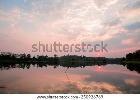 Tranquil lake and cloudy sky in sunset time - stock photo