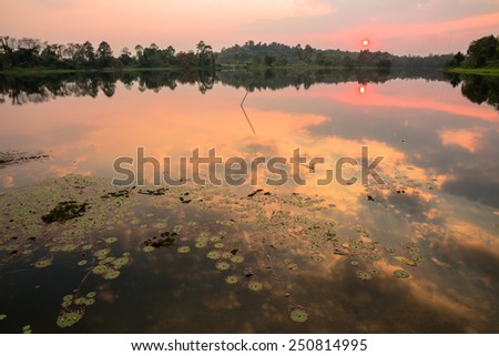 Tranquil lake and reflection cloudy sky in sunset time - stock photo