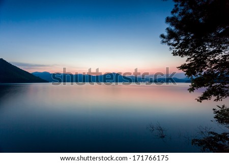Tranquil lake under the sunset - stock photo