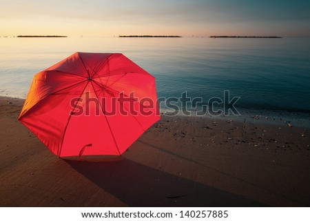 Tranquil Mediterranean morning seashore with beach umbrella - stock photo