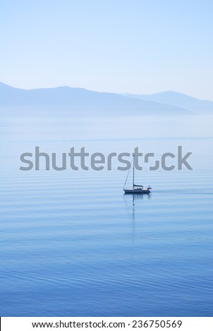 Tranquil morning sea with a sailing ship - stock photo