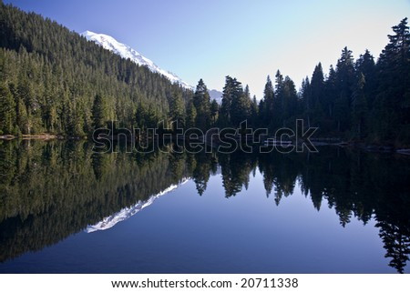 """Tranquil mountain lake with Mount Rainier peaking out from behind the hill and reflecting in the lake """"mount rainier national park"""" - stock photo"""