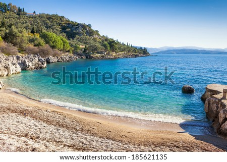 Tranquil Nissaki beach, a small cove lapped by limpid waters on the North-East coast of Corfu, Greece. - stock photo
