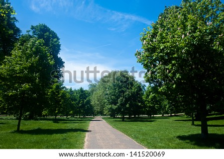 Tranquil pathway surrounded by luxuriant vegetation and trees in Hyde Park, London - stock photo