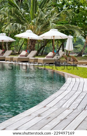 Tranquil pool at a tropical resort with a curving wooden deck leading to vacant recliner chairs and umbrellas for that idyllic summer vacation - stock photo