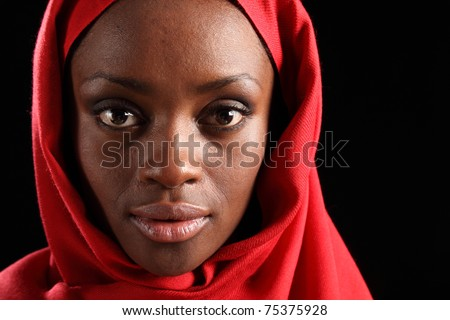 Tranquil portrait of beautiful young black african american woman wearing red hijab, taken against a black background. - stock photo