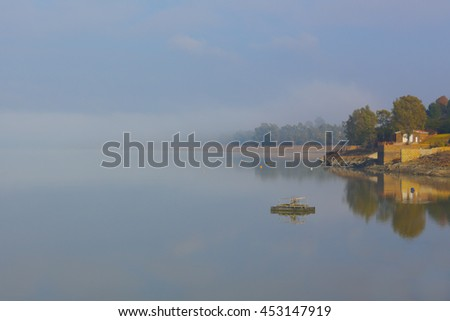 Tranquil, quiet and serene landscape setting at dawn with misty background on lake shore with boat house