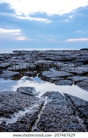 Tranquil rock pool on a rocky shoreline reflecting the cloudy sky in a marine and nautical background concept. - stock photo
