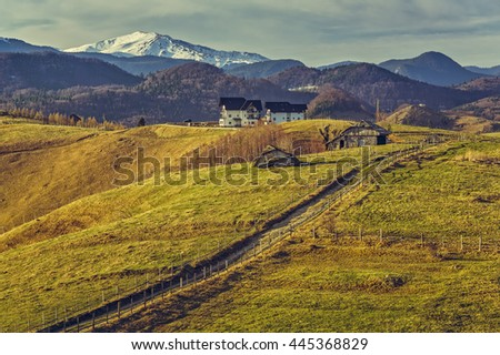 Tranquil rural view with country road and traditional wooden houses uphill in Sirnea village, Brasov county, Romania. Travel destinations. - stock photo