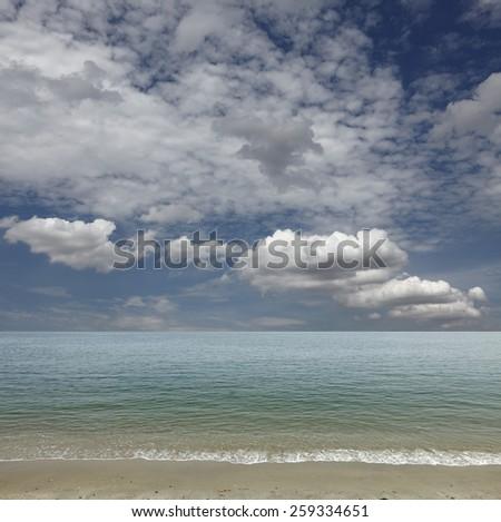 Tranquil sandy beach under a blue cloudy sky.  - stock photo
