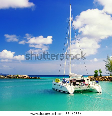 tranquil scene in sunny morning on Seychelles with sailing boat - stock photo